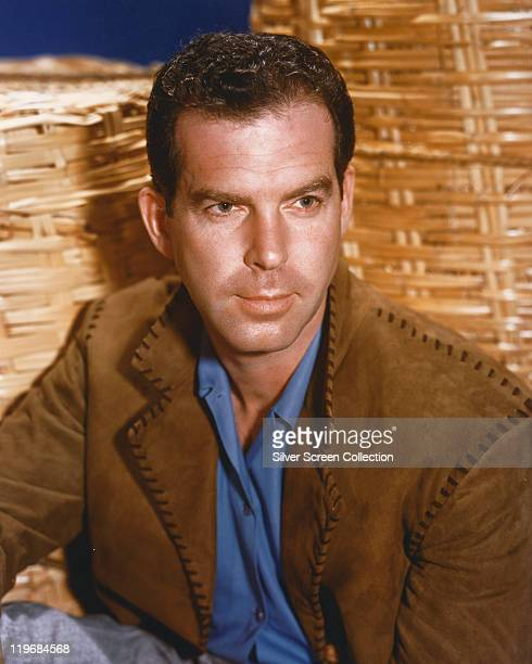 Fred MacMurray US actor wearing a blue shirt beneath a brown suede jacket against a wickerwork background circa 1950