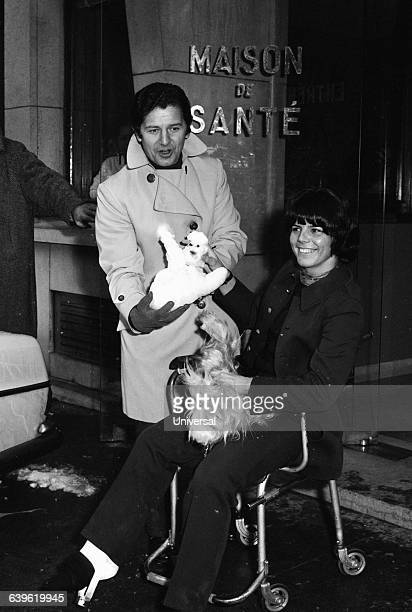Fred Mella member of group 'Les Compagnons de la Chanson' accompanies French skier Annie Famose as she leaves hospital after surgery