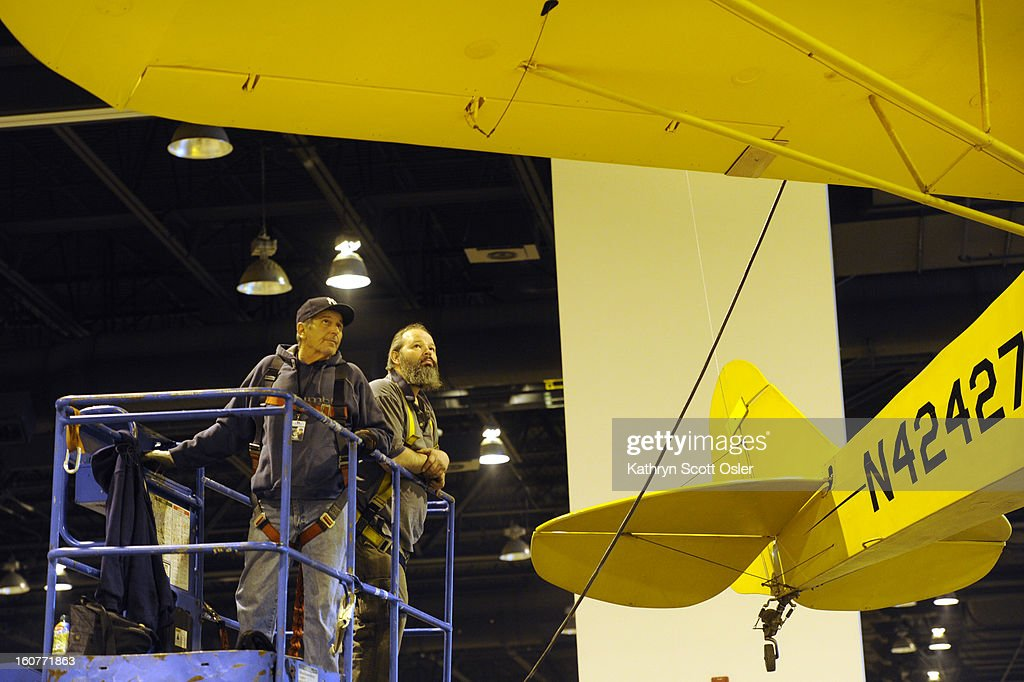 Fred Michelotti, left, and Allen Olmstead from Freeman Decorating, carefully position a Piper J-3 Cub up in the air. The Colorado Garden and Home Show has partnered with Wings Over the Rockies Air and Space Museum for the entry garden at the Colorado Convention Center. The museum for the first time has transported about half a dozen planes and gliders to help transform the 5,500-square-foot 'Flowers and Flight' garden for the 54th annual show. Matthew Burchette, curator for the museum, says this was a big deal to take the planes apart for transport to the show, as well as driving whole planes down Denver streets at midnight on flatbed trucks.