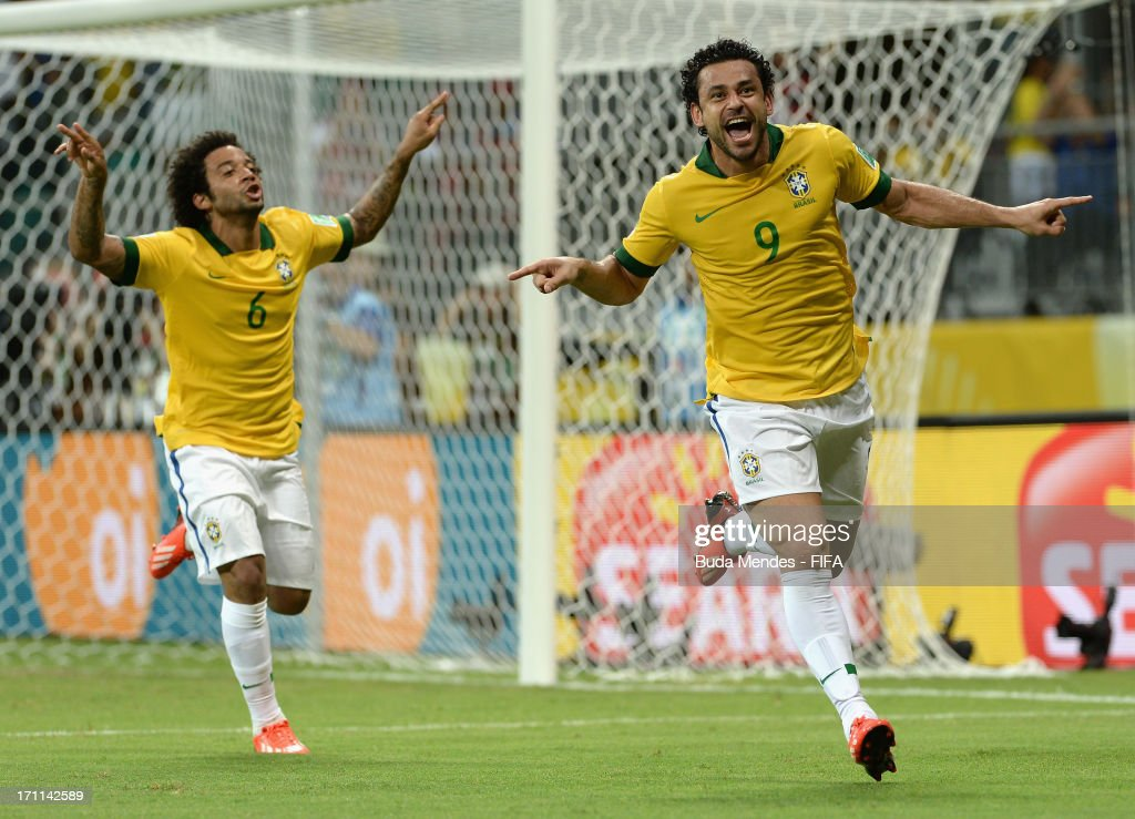 Fred of Brazil (9) celebrates with team mate Marcelo (6) as he scores their fourth goal during the FIFA Confederations Cup Brazil 2013 Group A match between Italy and Brazil at Estadio Octavio Mangabeira (Arena Fonte Nova Salvador) on June 22, 2013 in Salvador, Brazil.