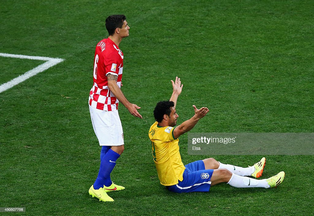 Fred of Brazil gestures for a foul from the ground as <a gi-track='captionPersonalityLinkClicked' href=/galleries/search?phrase=Dejan+Lovren&family=editorial&specificpeople=5577379 ng-click='$event.stopPropagation()'>Dejan Lovren</a> of Croatia looks on in the second half during the 2014 FIFA World Cup Brazil Group A match between Brazil and Croatia at Arena de Sao Paulo on June 12, 2014 in Sao Paulo, Brazil.