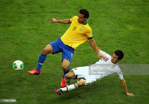Fred of Brazil is tackled by Yasuyuki Konno of Japan during the FIFA Confederations Cup Brazil 2013 Group A match between Brazil and Japan at...