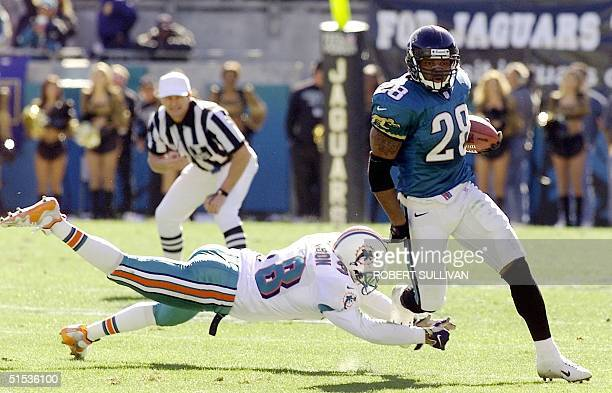 Fred Taylor of the Jacksonville Jaguars runs past a diving Calvin Jackson of the Miami Dolphins during the first half 15 January 2000 in their AFC...