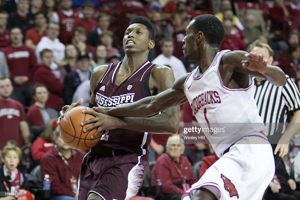 Fred Thomas #1 of the MIssissippi State Bulldogs is hit in the arm by Mardracus Wade #1 of the Arkansas Razorbacks at Bud Walton Arena on January 23, 2013 in Fayetteville, Arkansas. The Razorbacks defeated the Bulldogs 96-70.