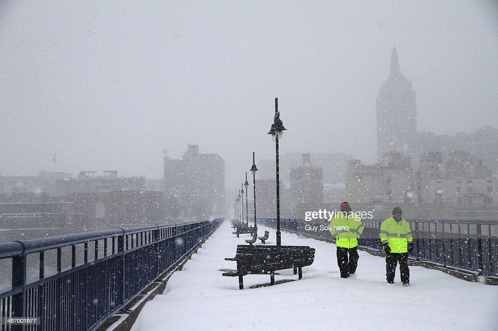 Fred Van Orden, left, and Andy Santell, members of Downtown Rochester Special Services, walk across the Pont de Rennes bridge during a snow storm on February 5, 2014 in Rochester, New York. An additional foot of snow blanketed Western New York overnight in the latest winter storm system that has affected areas from Kansas to Maine.