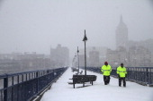 Fred Van Orden left and Andy Santell members of Downtown Rochester Special Services walk across the Pont de Rennes bridge during a snow storm on...