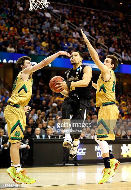 Fred VanVleet of the Wichita State Shockers drives to the basket against Steve Vasturia and Pat Connaughton of the Notre Dame Fighting Irish in the...