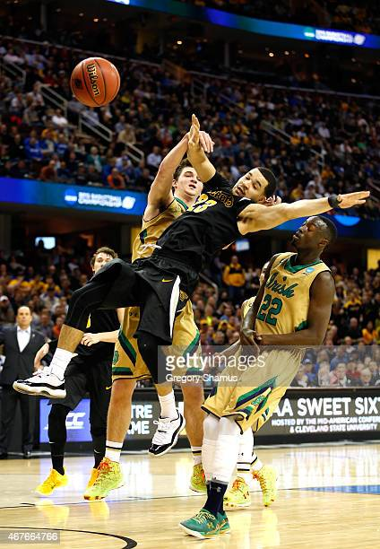 Fred VanVleet of the Wichita State Shockers drives to the basket against Steve Vasturia and Jerian Grant of the Notre Dame Fighting Irish in the...