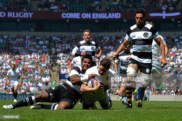 Freddie Burns of England crashes through the tackle from Takudzwa Ngwenya of The Barbarians to score the opening try during the rugby union...