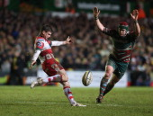Freddie Burns of Gloucester kicks past Marcos Ayerza during the Aviva Premiership match between Leicester Tigers and Gloucester at Welford Road on...
