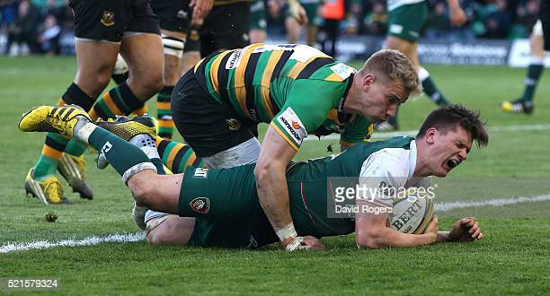 Freddie Burns of Leicester grimaces as Harry Mallinder falls on him as he scores a try during the Aviva Premiership match between Northampton Saints...