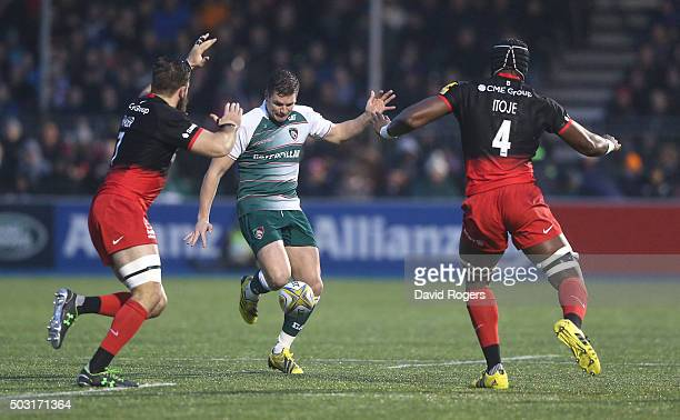 Freddie Burns of Leicester kicks the ball past Maro Itoje and Will Fraser during the Aviva Premiership match between Saracens and Leicester Tigers at...