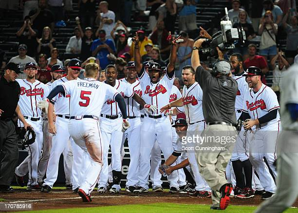 Freddie Freeman of the Atlanta Braves arrives at home plate after hitting a ninth inning gamewinning home run against the New York Mets at Turner...