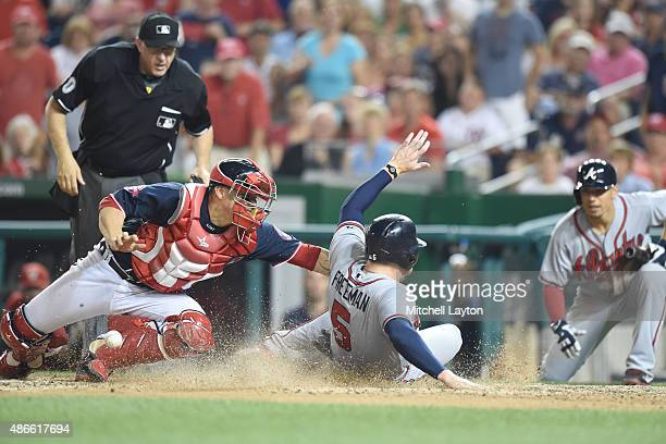 Freddie Freeman of the Atlanta Braves beats tag from Jose Lobaton of the Washington Nationals to tie the game in the eight inning on a Nick Swisher...