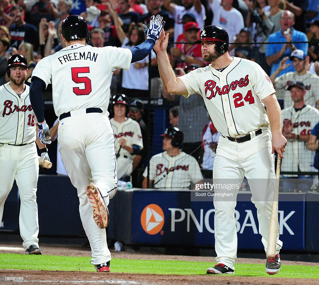 Freddie Freeman #5 of the Atlanta Braves is congratulated by Evan Gattis #24 after hitting a sixth inning solo home run against the San Diego Padres at Turner Field on September 14, 2013 in Atlanta, Georgia.