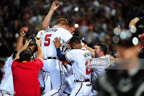Freddie Freeman of the Atlanta Braves is congratulated by teammates after hitting a 9th inning walk off home run against the Miami Marlins at Turner...