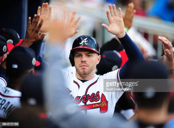 Freddie Freeman of the Atlanta Braves is congratulated by teammates after scoring a first inning run against the Toronto Blue Jays at SunTrust Park...