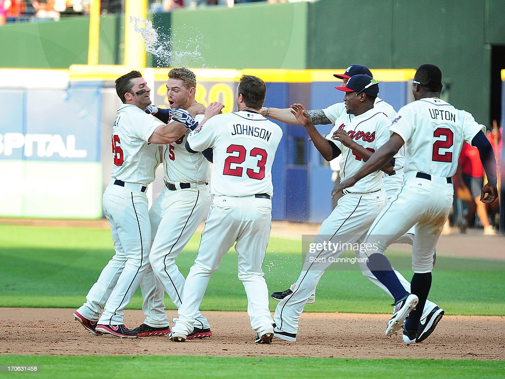 Freddie Freeman #5 of the Atlanta Braves is mobbed by teammates after knocking in the game-winning run in the ninth inning against the San Francisco Giants at Turner Field on June 15, 2013 in Atlanta, Georgia.