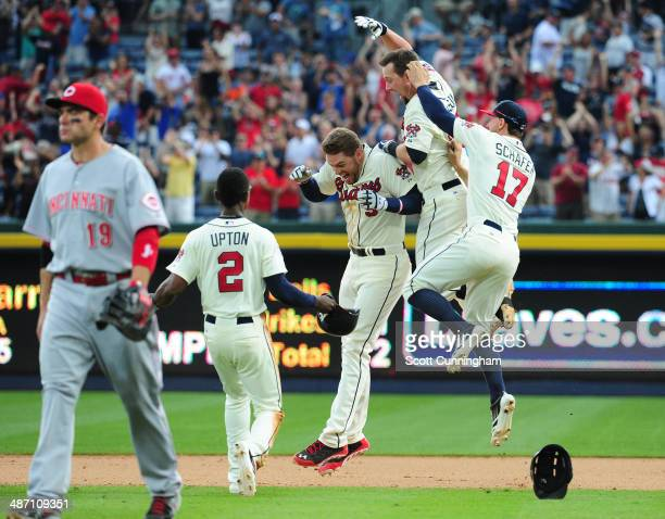 Freddie Freeman of the Atlanta Braves is mobbed by teammates after knocking in the gamewinning run in the 10th inning against the Cincinnati Reds at...