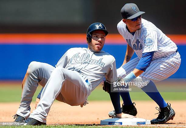 Freddie Freeman of the Atlanta Braves is safe at third base during the third inning ahead of the tag from Wilmer Flores of the New York Mets at Citi...