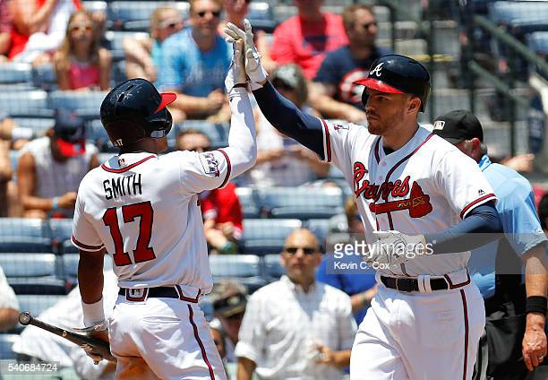 Freddie Freeman of the Atlanta Braves reacts after hitting a tworun homer in the third inning to score Mallex Smith against the Cincinnati Reds at...
