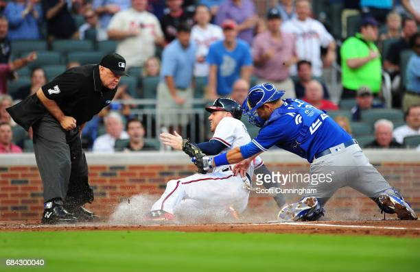 Freddie Freeman of the Atlanta Braves scores a first inning run against Luke Maile of the Toronto Blue Jays at SunTrust Park on May 17 2017 in...