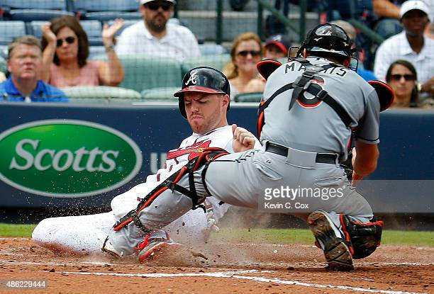 Freddie Freeman of the Atlanta Braves scores past the tag of Jeff Mathis of the Miami Marlins on a twoRBI single hit by Hector Olivera in the third...