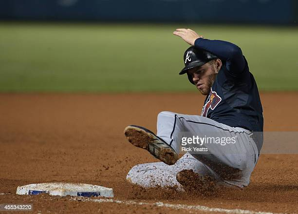 Freddie Freeman of the Atlanta Braves slides in safe to third on a overthrow to stealing second base in the eighth inning against the Texas Rangers...