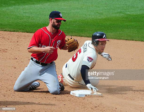 Freddie Freeman of the Atlanta Braves slides in to second base for a double against Kevin Frandsen of the Washington Nationals at Turner Field on...