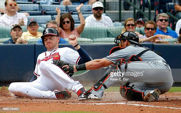 Freddie Freeman of the Atlanta Braves slides safely past the tag of Jeff Mathis of the Miami Marlins on a twoRBI single hit by Hector Olivera in the...