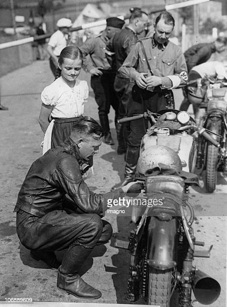 Freddie Frith with his motorycle and a little girl He gets prepared for the training for the Grand Prix of Germany at the Sachsenring in...