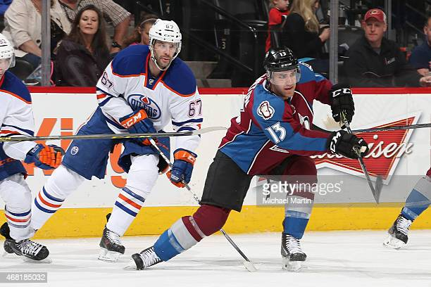 Freddie Hamilton of the Colorado Avalanche passes the puck as he is pursued by Benoit Pouliot of the Edmonton Oilers at the Pepsi Center on March 30...
