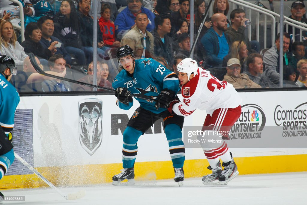 Freddie Hamilton of the San Jose Sharks clears the puck against Brandon Yip of the Phoenix Coyotes during a preseason NHL game at SAP Center on...