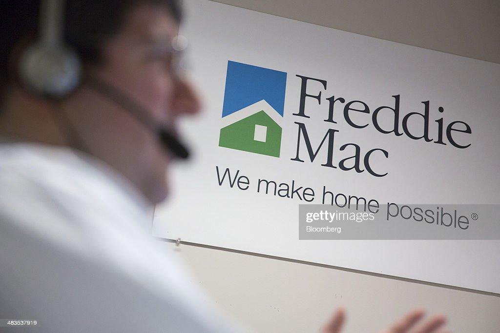 A Freddie Mac sign hangs behind employee John Estrada as he works in the borrower contact unit area at Freddie headquarters in McLean Virginia US on...