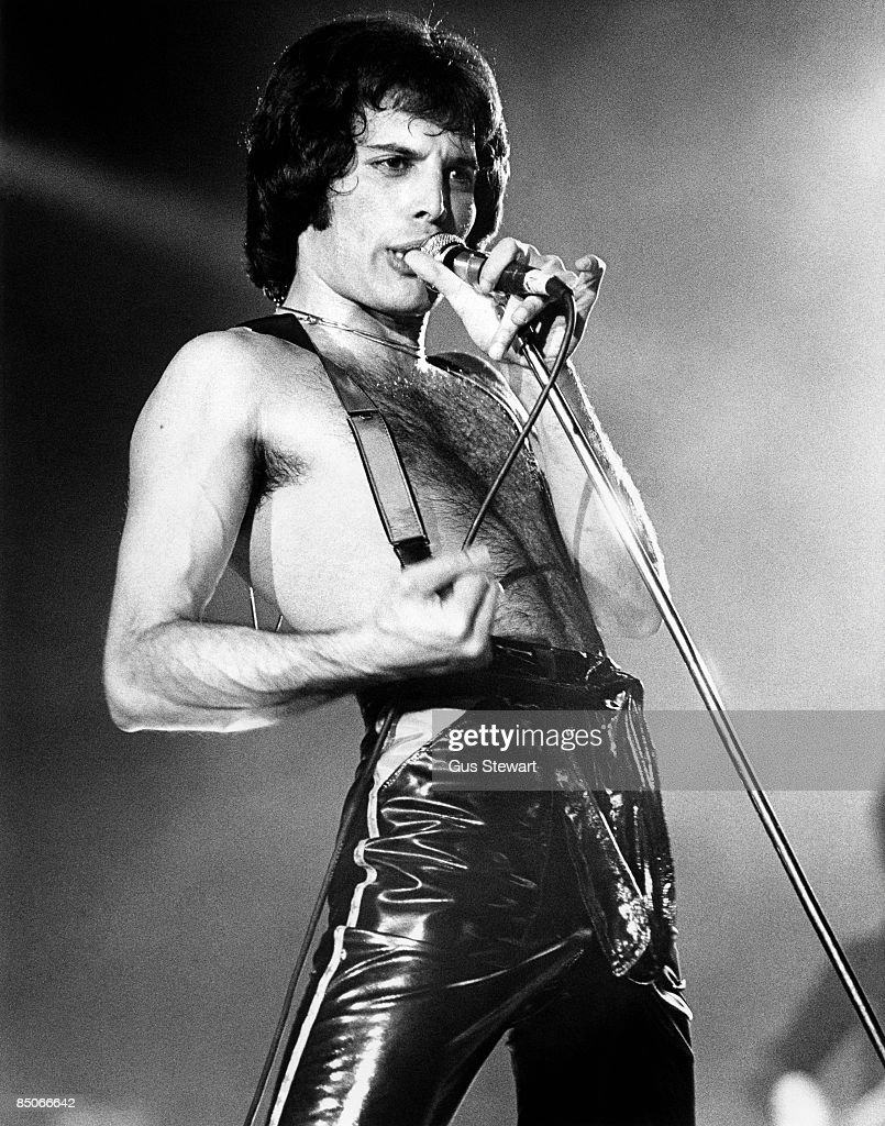 Photo of QUEEN; Freddie Mercury performing live on stage , barechested and wearing braces