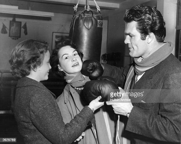 Freddie Mills exworld heavyweight boxing champion handing over his gloves to two students of the Queen Mary College They are securing articles from...