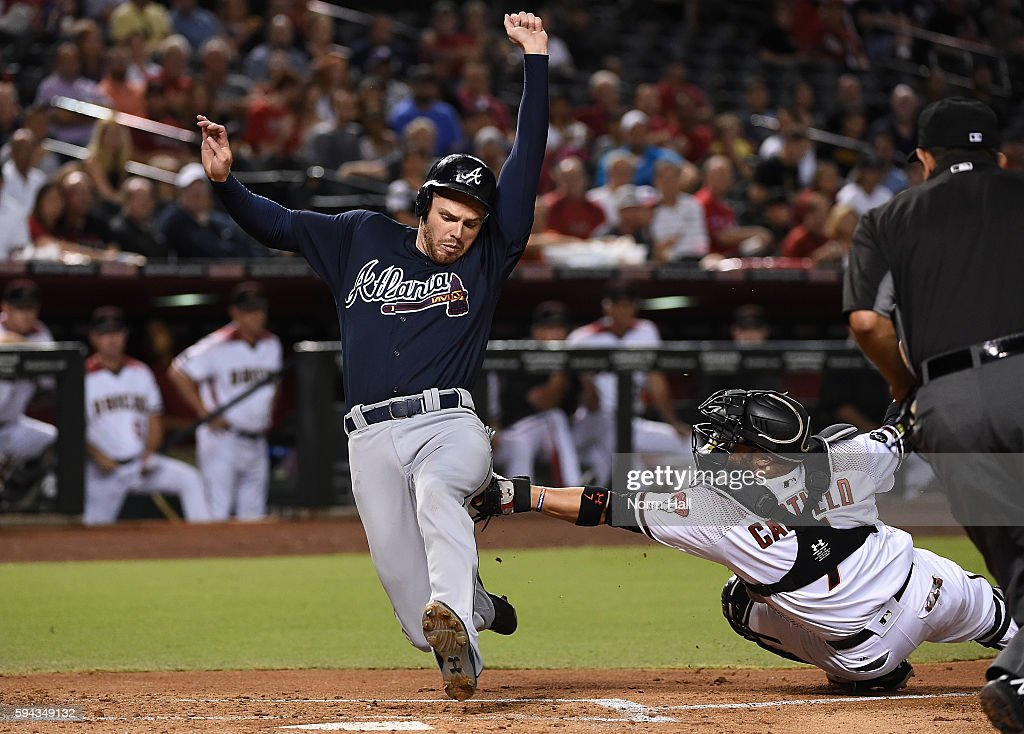 Freddy Freeman of the Atlanta Braves is tagged out at home plate by Welington Castillo of the Arizona Diamondbacks during the second inning at Chase...