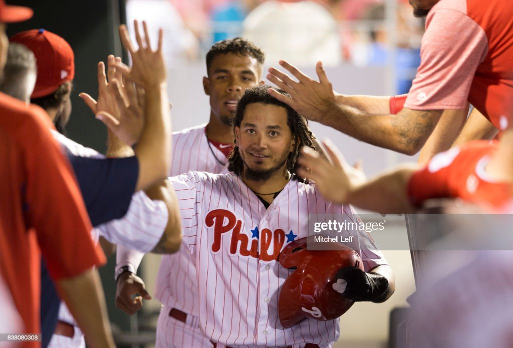 Freddy Galvis #13 and Nick Williams #5 of the Philadelphia Phillies high five teammates in the dugout after both scored a run in the bottom of the sixth inning against the Miami Marlins at Citizens Bank Park on August 23, 2017 in Philadelphia, Pennsylvania. The Phillies defeated the Marlins 8-0.
