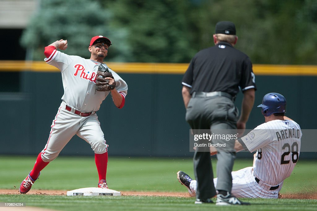 Freddy Galvis #13 of the Philadelphia Phillies attempts to turn a double play past a sliding Nolan Arenado #28 of the Colorado Rockies in the first inning of a game at Coors Field on June 15, 2013 in Denver, Colorado. The Rockies led 6-1 after one inning.