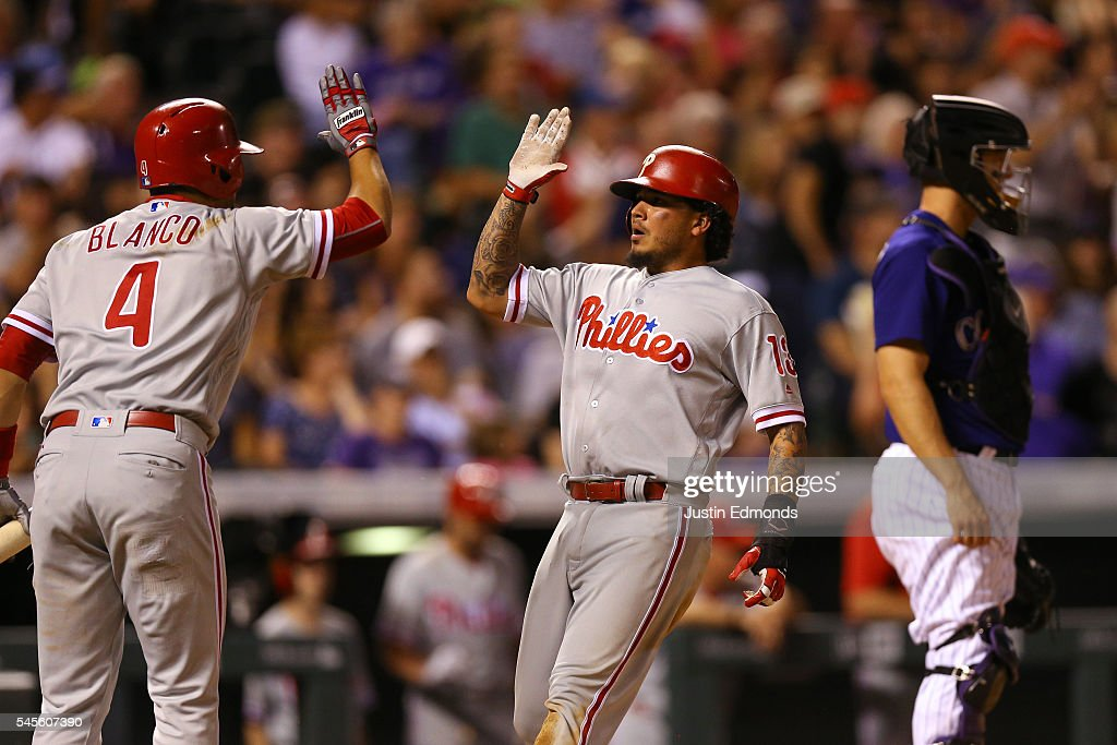 Freddy Galvis #13 of the Philadelphia Phillies celebrates with Andres Blanco #4 after he scored on a throwing error by Nick Hundley #4 of the Colorado Rockies during the ninth inning at Coors Field on July 8, 2016 in Denver, Colorado. The Phillies defeated the Rockies 5-3.