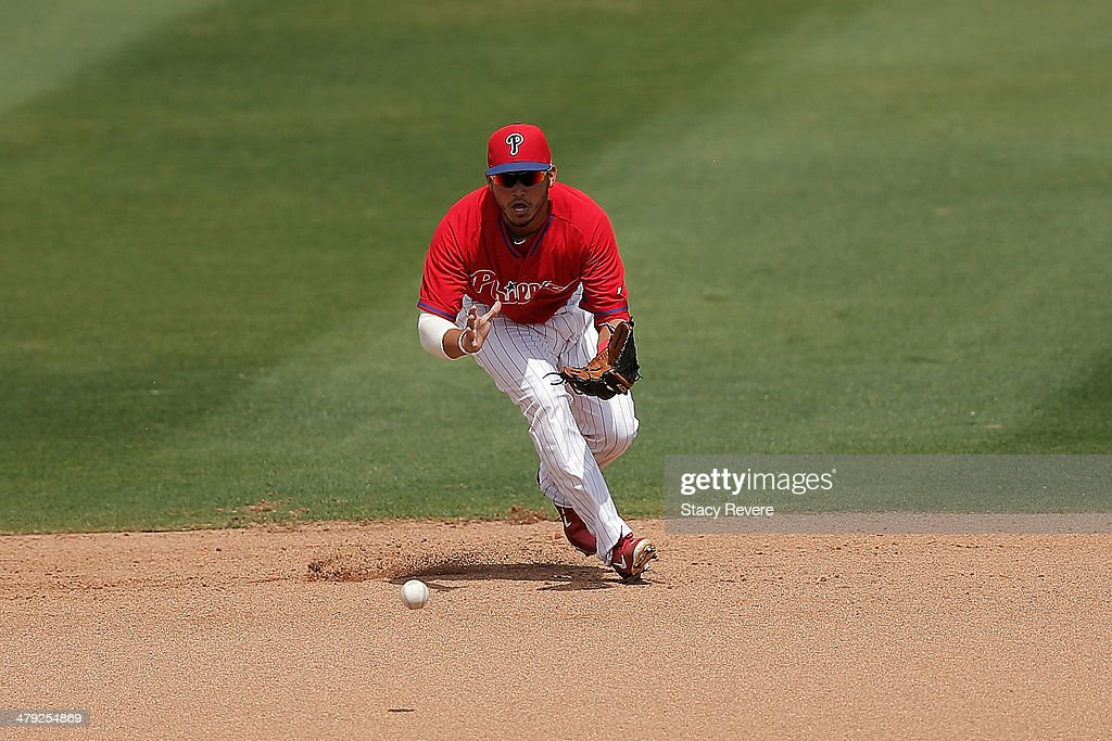 Freddy Galvis #13 of the Philadelphia Phillies fields a ball in the third inning of a game against the Pittsburgh Pirates at Bright House Field on March 16, 2014 in Clearwater, Florida. Pittsburgh won the game 5-0.