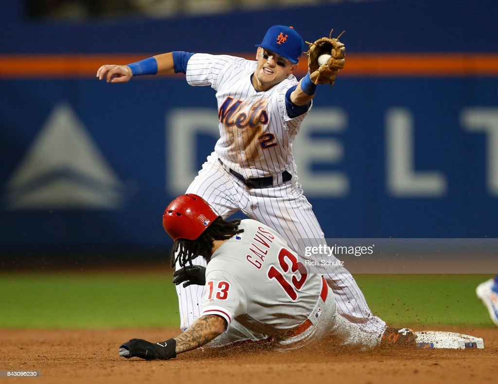 Freddy Galvis #13 of the Philadelphia Phillies is caught stealing as Gavin Cecchini #2 of the New York Mets gets set to make the tag during the third inning of a game at Citi Field on September 5, 2017 in the Flushing neighborhood of the Queens borough of New York City.