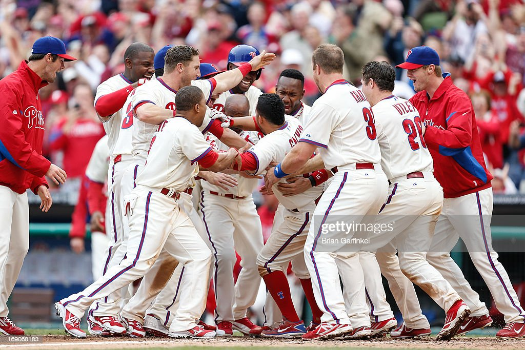 Freddy Galvis #13 of the Philadelphia Phillies is congratulated by teammates at home plate after hitting a home run in the bottom of the ninth inning to win the game against the Cincinnati Reds at Citizens Bank Park on May 19, 2013 in Philadelphia, Pennsylvania. The Phillies won 3-2.