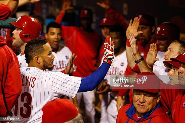Freddy Galvis of the Philadelphia Phillies is congratulated by teammates in the dugout after hitting a solo home run in the tenth inning of the game...