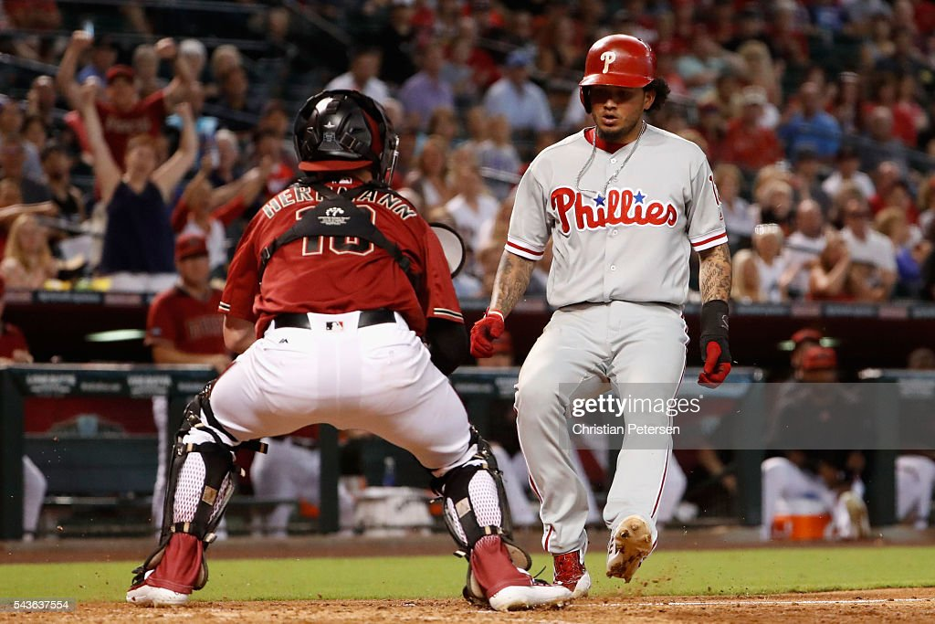 Freddy Galvis of the Philadelphia Phillies is tagged out at home plate by catcher Chris Herrmann of the Arizona Diamondbacks during the fourth inning...