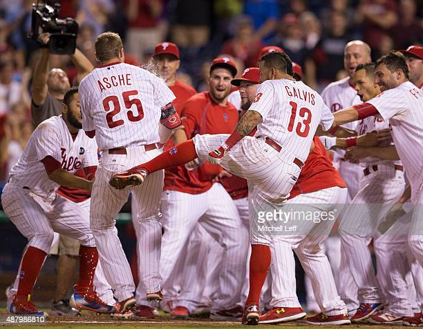 Freddy Galvis of the Philadelphia Phillies kicks the behind of Cody Asche after Asche hit a walkoff tworun home run in the bottom of the ninth inning...