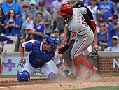 Freddy Galvis of the Philadelphia Phillies scores a run in the 9th inning as Miguel Montero of the Chicago Cubs attempts the tag at Wrigley Field on...