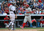 Freddy Galvis of the Philadelphia Phillies scores as catcher Jordan Pacheco of the Colorado Rockies looks on in the eighth inning at Coors Field on...