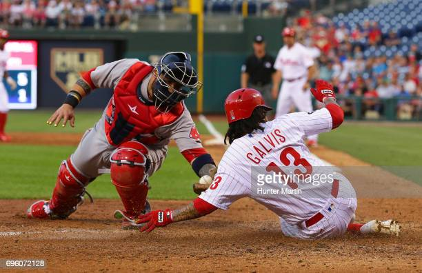Freddy Galvis of the Philadelphia Phillies slides home safely in front of the tag by Sandy Leon of the Boston Red Sox in the third inning during a...
