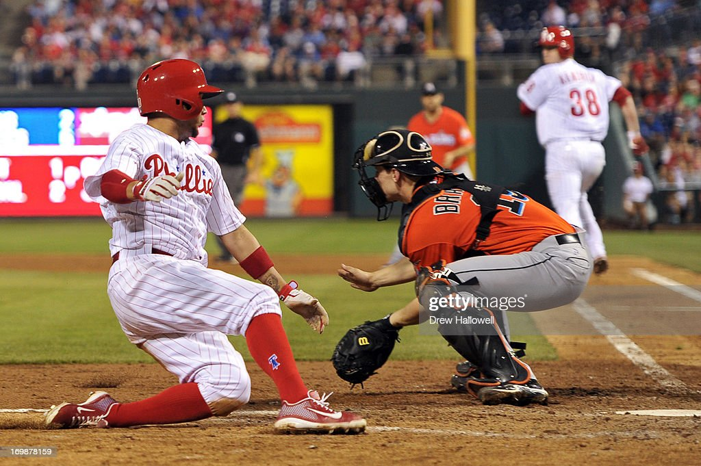 Freddy Galvis #13 of the Philadelphia Phillies slides safe into home past Rob Brantly #19 of the Miami Marlins on a sacrifice hit by <a gi-track='captionPersonalityLinkClicked' href=/galleries/search?phrase=Kyle+Kendrick&family=editorial&specificpeople=4365300 ng-click='$event.stopPropagation()'>Kyle Kendrick</a> #38 at Citizens Bank Park on June 3, 2013 in Philadelphia, Pennsylvania. The Phillies won 7-2.